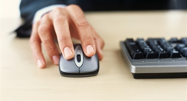 Mans hand on computer mouse